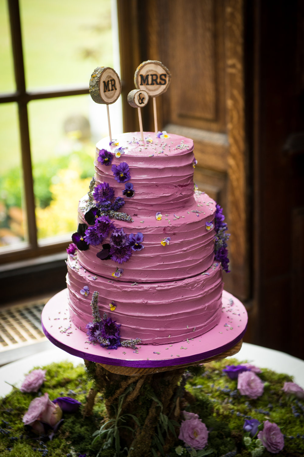mauve buttercream wedding cake with edible flowers