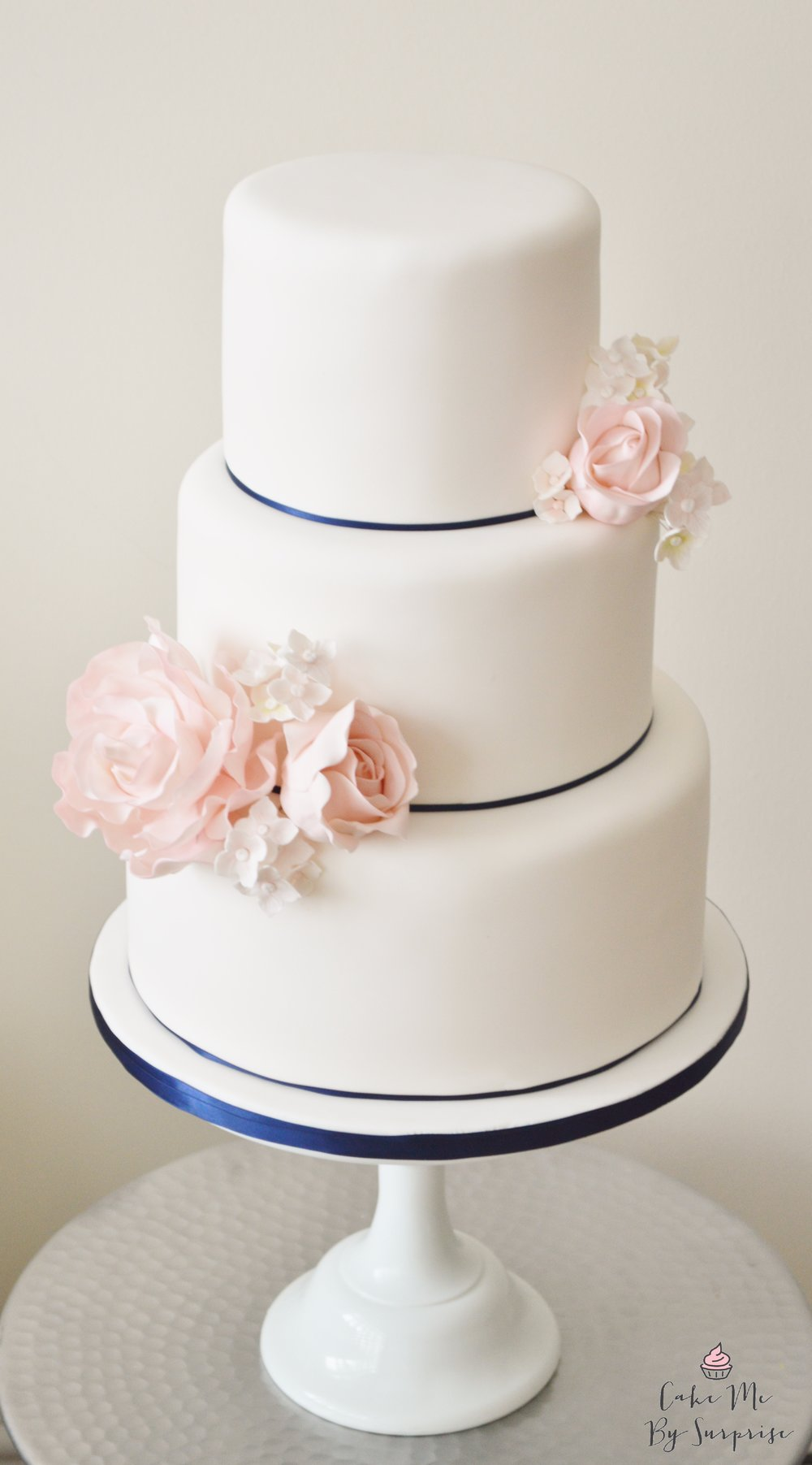 Three tier white and pink flowers wedding cake with navy trim