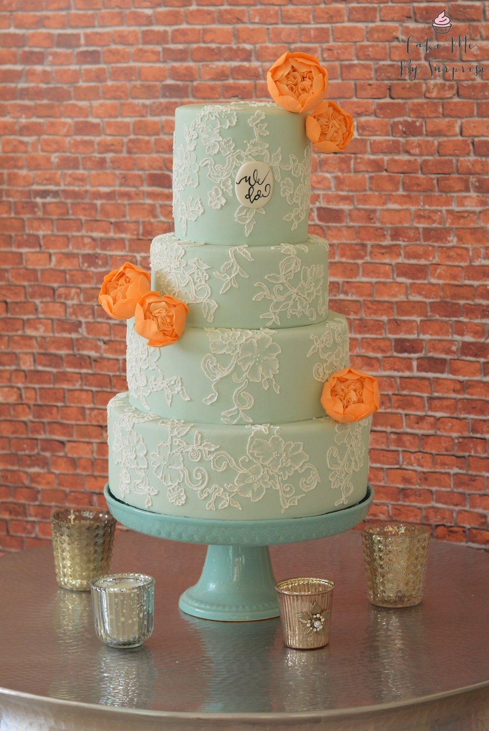Sage Green and Peach Calligraphy Wedding Cake A four tier sage green wedding cake complete with hand piped lace design, handcrafted 'David Austin' cabbage roses and a special plaque finished in 'We Do' calligraphy. Serves 215 £820