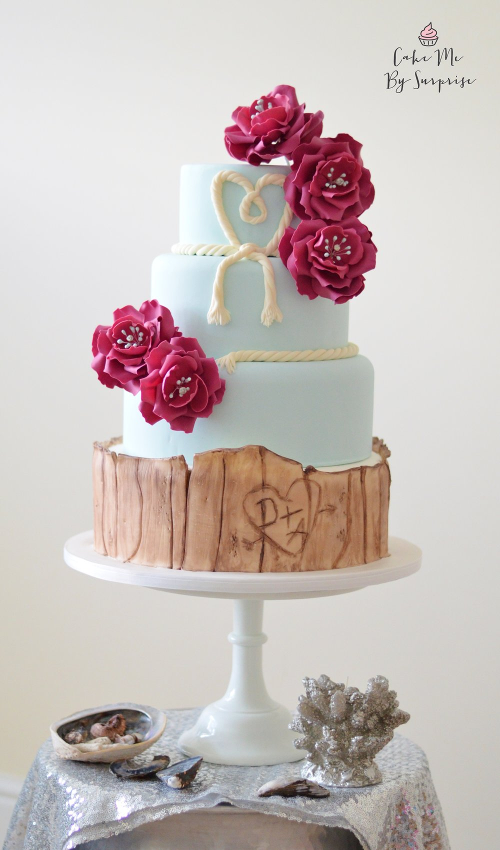 Drift Wood Wedding Cake  Serves 130 (dessert size) 212 (coffee size) A four tier wedding cake completed with edible drift wood base tier, that can be personalized with the bride and grooms initials. A 'tie the knot' rope heart has been wrapped around the top tier, and to finish beautiful handcrafted sugar flowers cascade down this blue fondant cake.  £645
