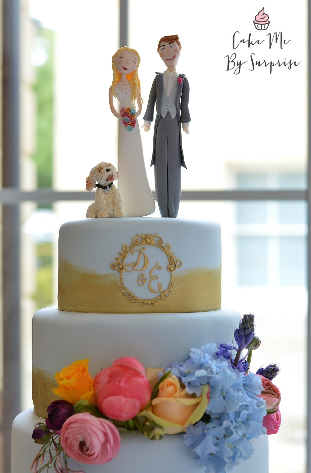 blue and gold wedding cake with bright coloured flowers