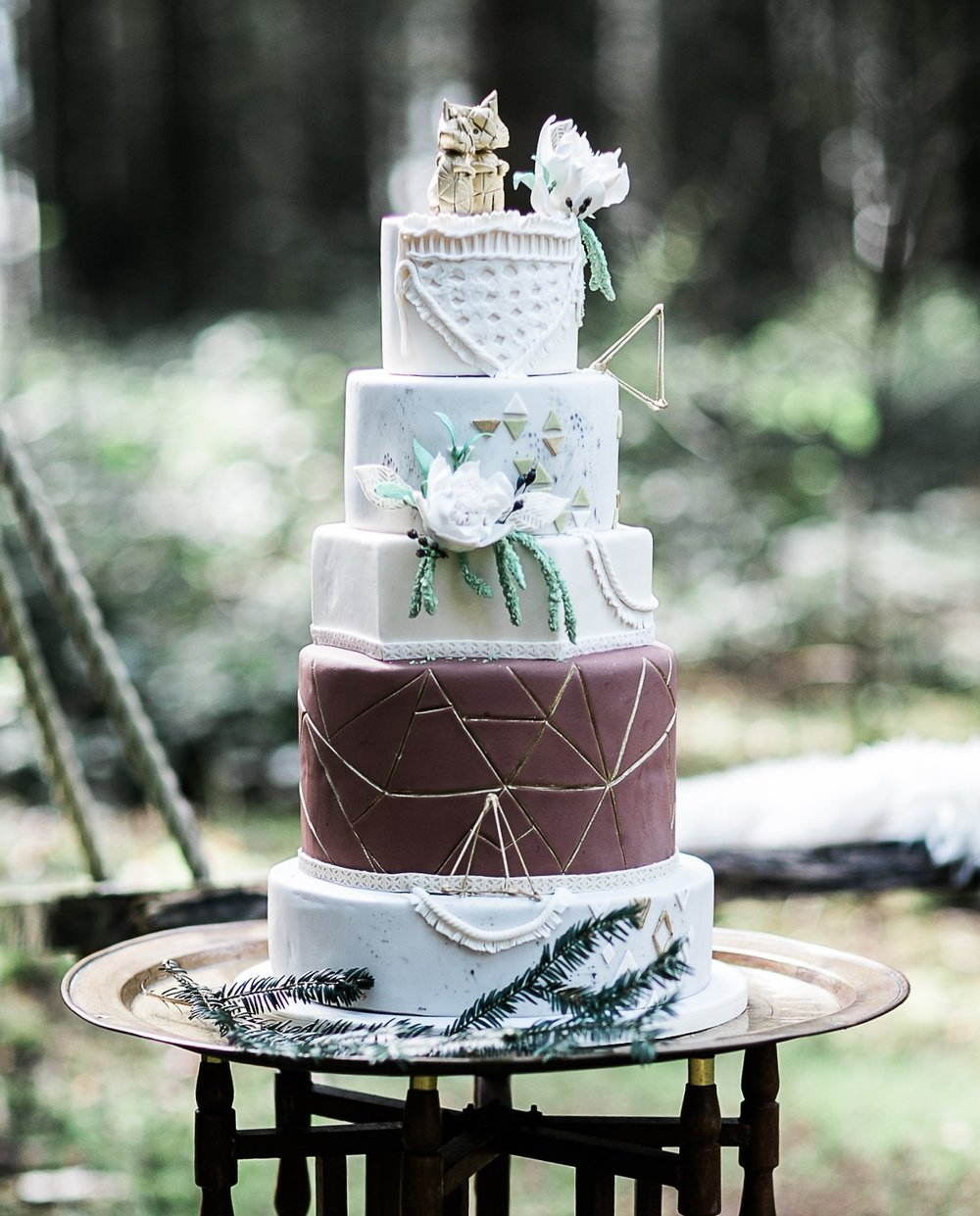 Photo Credit SamieLeePhotography Boho Woodland Wedding Cake 5 Tier wedding cake completed with edible macrame trim, hand crafted geometric gold foxes and white sugar proteas and berries. Serves 200 £760