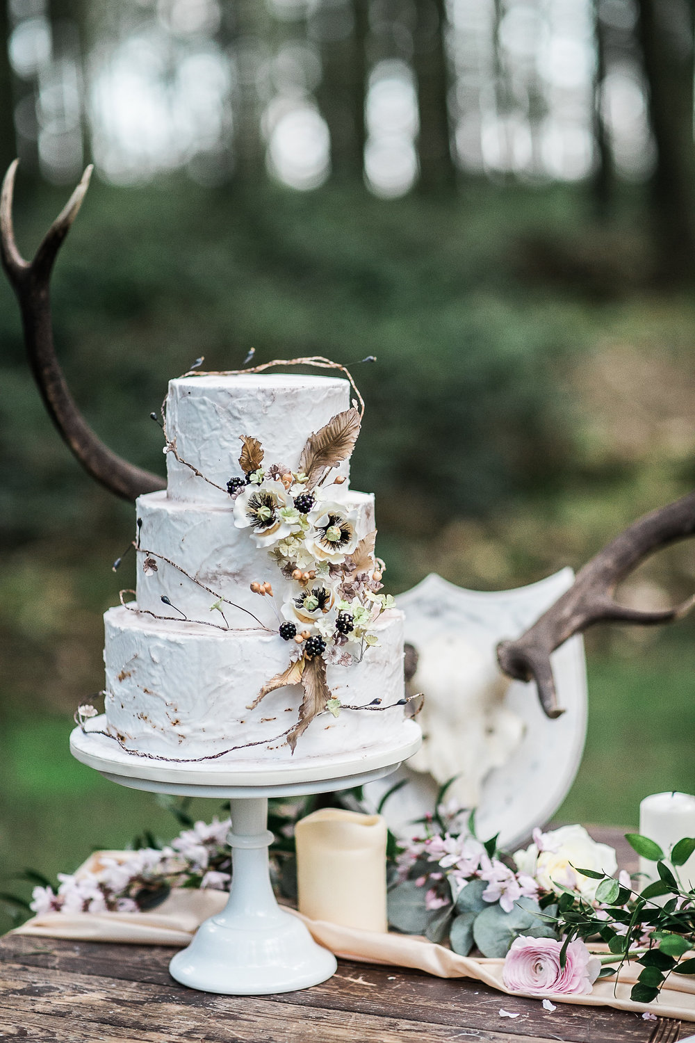 Photo credit SamieleePhotography/ Styled shoot NatashaSpencerEvents Three Tier white royal icing finished cake, with handcrafted winter berries, poppies, feathers and vines.  Serves 80 £420