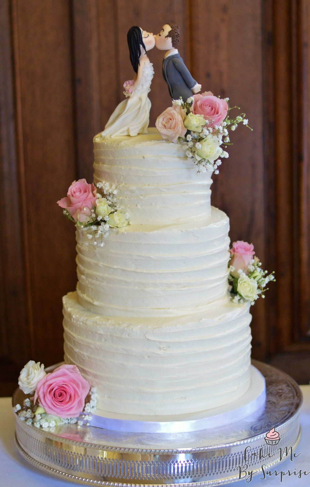Buttercream delight A three tier wedding cake finished in a coating of delicious ruffled buttercream. Completed with fresh flowers ( supplied by chosen florist) Handmade toppers created as bespoke design £320 - £420 +