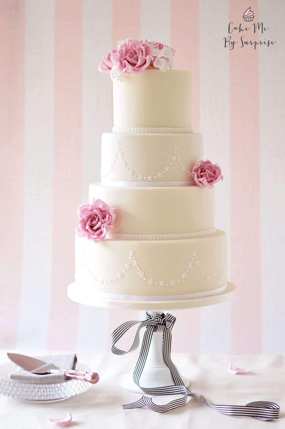 La Vie En Rose - Ivory and Pink Rose Wedding Cake A classic and elegant ivory wedding cake, finished with piped daisy tiers and handcrafted tea roses in dusty pink. Serves 180+ £640