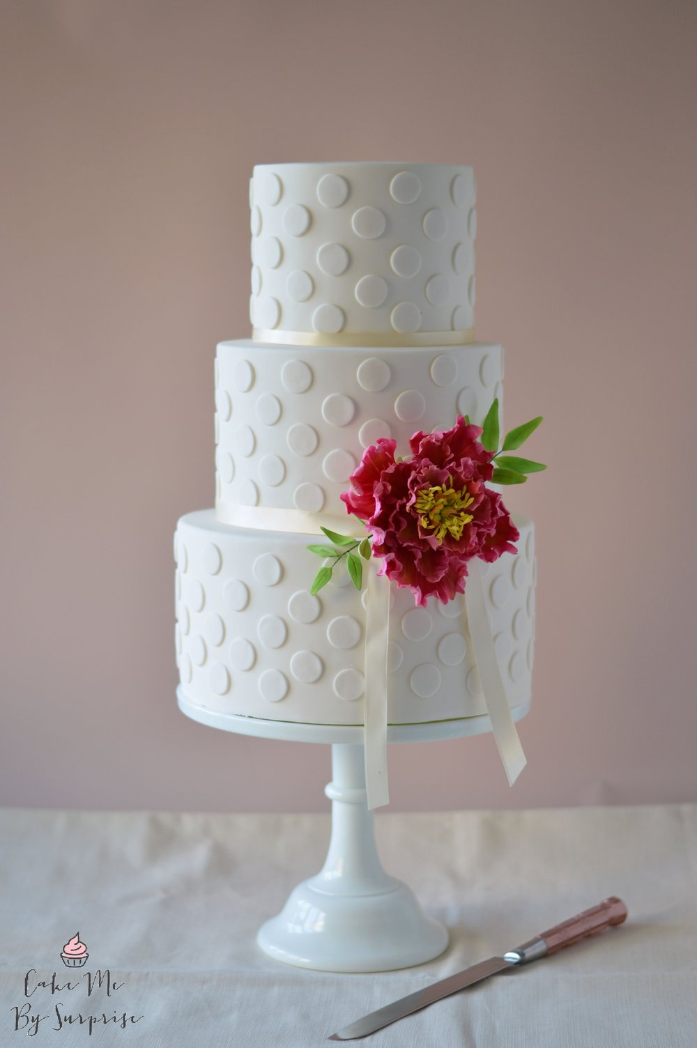 Poka Dots and Peony White Wedding Cake A simple three tier white poka dot wedding cake with statement sugar peony in a vibrant fuchsia pink. Serves 145 £450