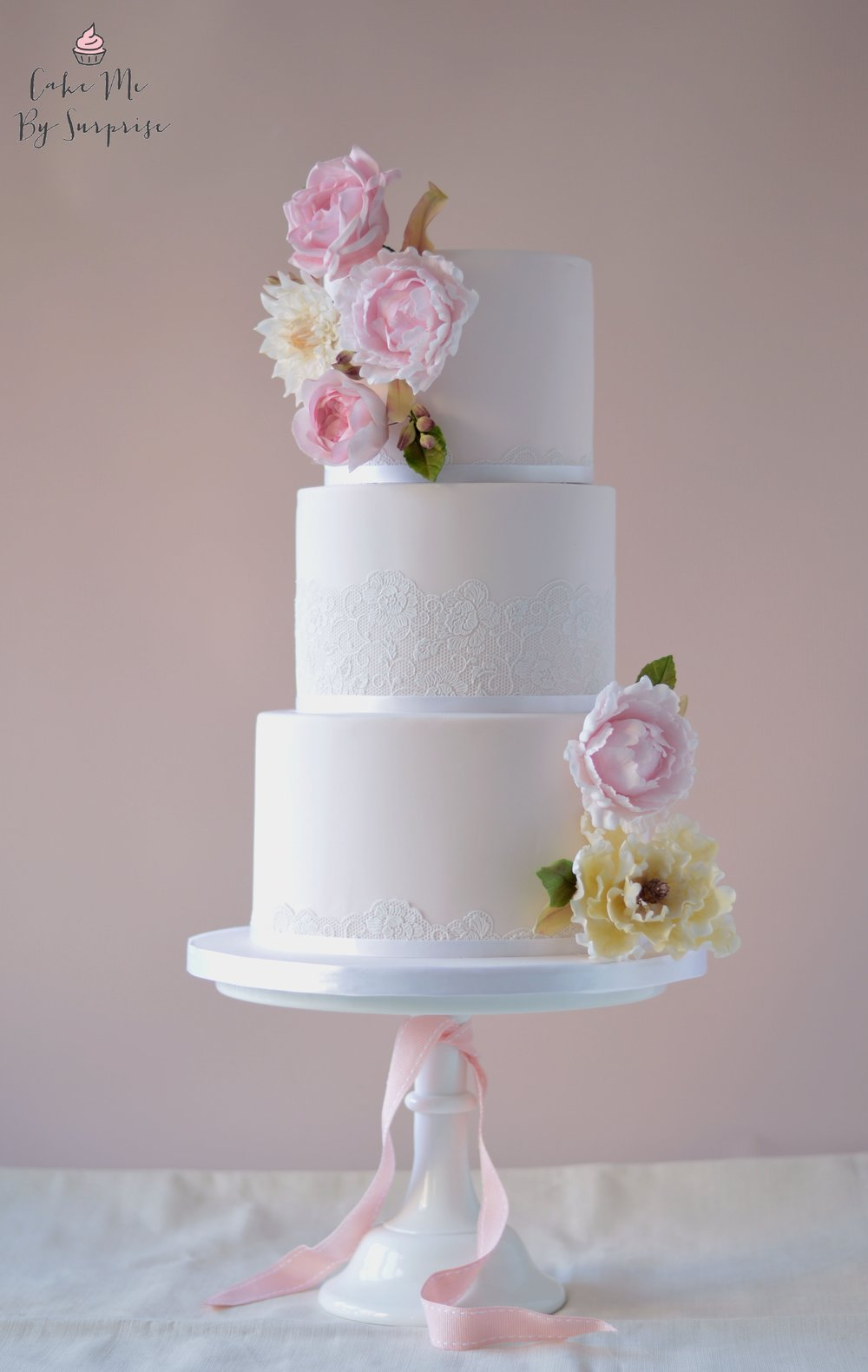 Sweet Love - Dusty Pink Floral Wedding Cake A three tier blush pink finished cake, with edible lace trim and handcrafted sugar flower blooms. Serves 130 £450