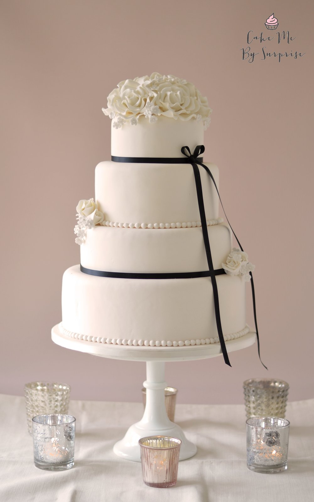 Emily - Classic White Wedding Cake A classic and elegant ivory finished four tier wedding cake with hand crafted white sugar roses, buds, and blossoms. Finished with a pearl boarder and black stain ribbon. Serves 218 £620