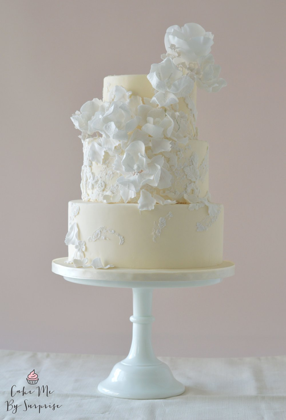 Vanity Fair- Ivory White Wedding Cake Bringing couture design to the forefront, this ivory finished cake is whimsical in feel, with a spray of white sugar flowers dancing upon the cake. Serves 70 £435