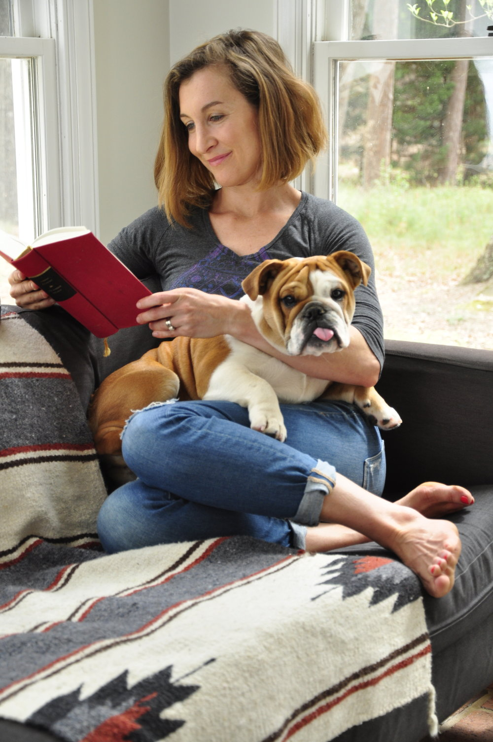A happy full life is reading a book while you force your dog to cuddle with you.