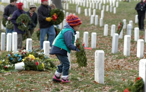Child Placing Wreath on Graves