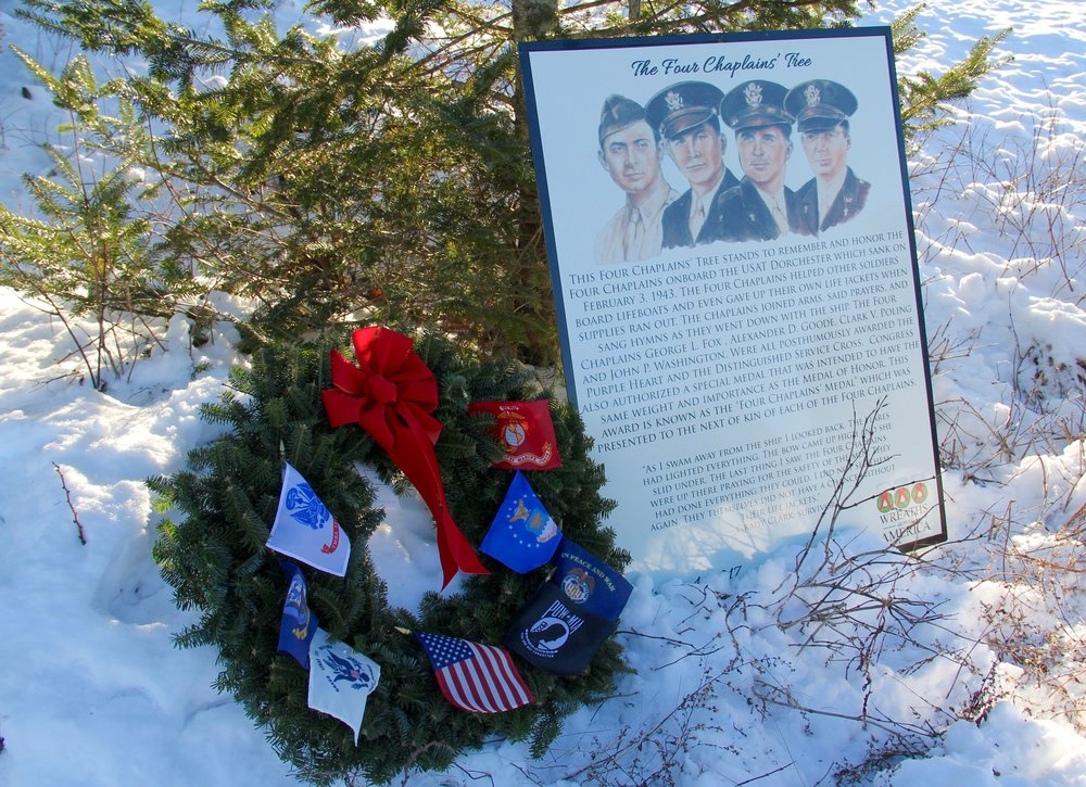 "The Four Chaplains Tree is on the tip land across from the Balsam Valley Chapel. In 2017 as part of the WAA Stem to Stone program replica dog tags for each of the Chaplains were placed among the branches of a rugged balsam fir from which the ""tips"" will one day be harvested to produce a veterans' remembrance wreath."