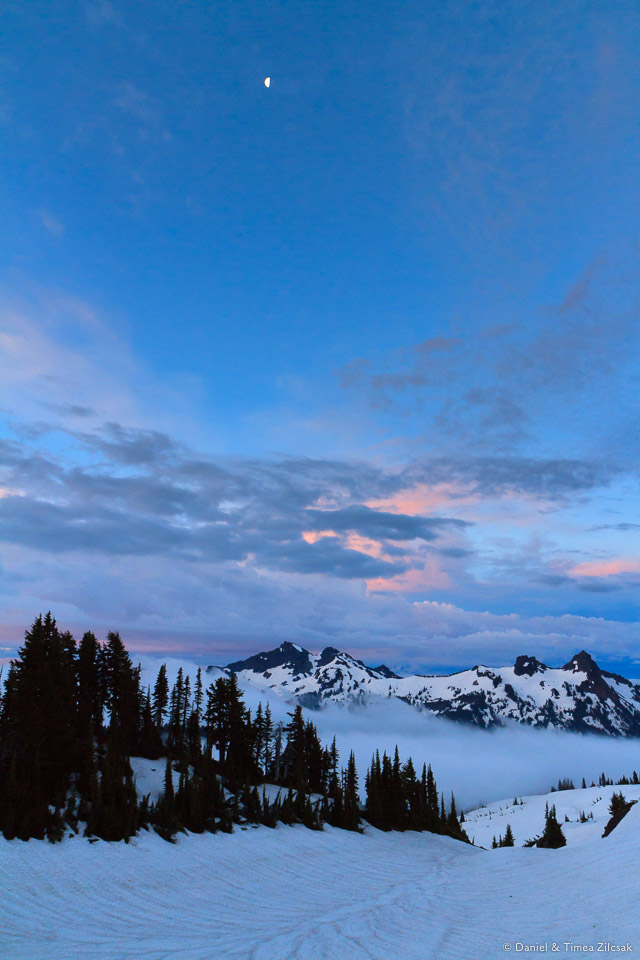 Moon over Tatoosh Range before sunrise. Clouds over Paradise and the lower mountain, Mount Rainier National Park