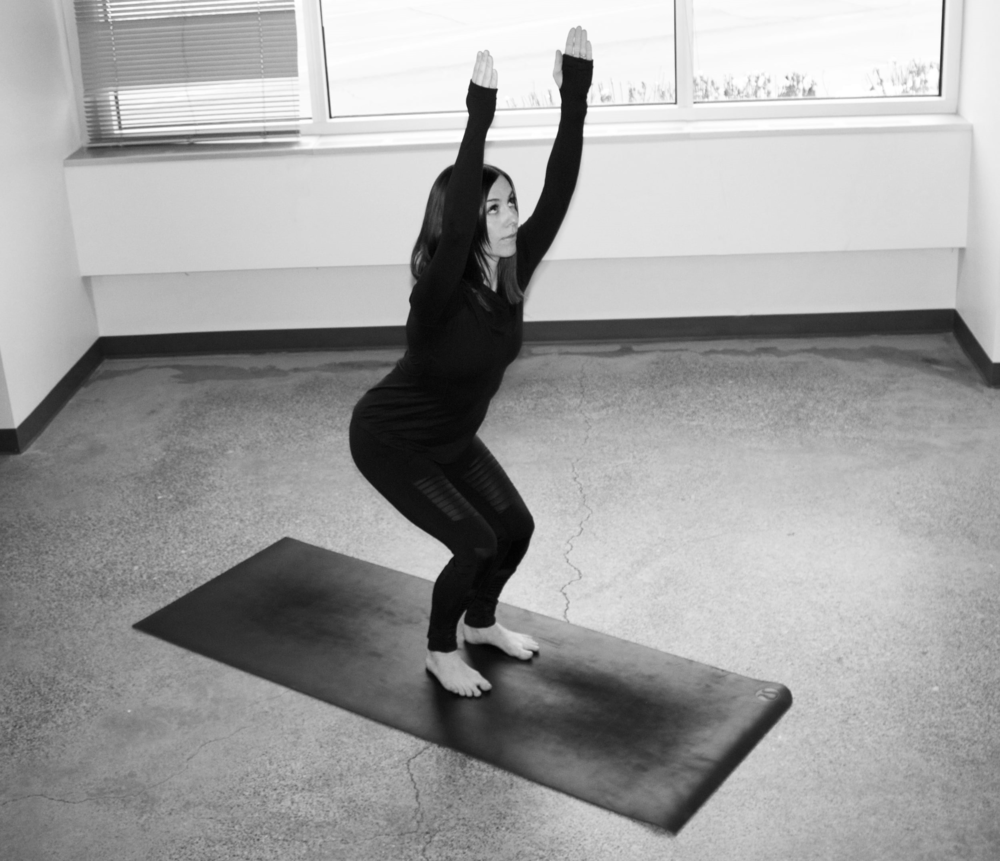 Stand with your feet about hip-width distance apart to practice this ski stance variation of Fierce pose. Bend your knees and sit your hips back, like you're sitting in a chair, and reach your arms up. Gaze up to your fingertips.