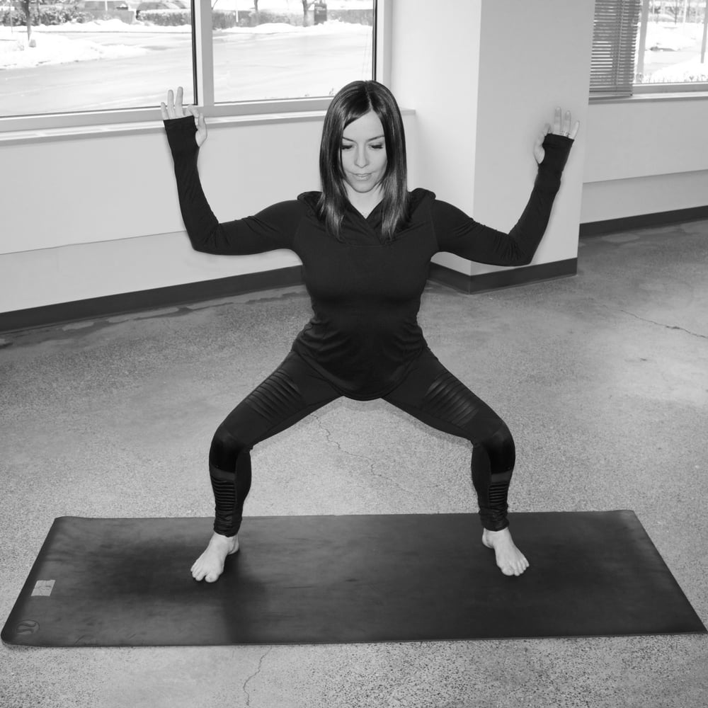 Step your feet widely apart, approximately 3 or more feet. Bend your knees and sit your hips back. bring your arms to a T, and then bend your elbows about 90 degrees to reach your hands toward the ceiling, making your arms look like a football goal post.