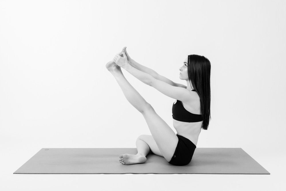 HERON    Bring your left leg through center, then gently use your hands and start to press your leg towards straight.    When you're ready, draw the soles of your feet to touch and repeat the same four postures again, this time on the other side.
