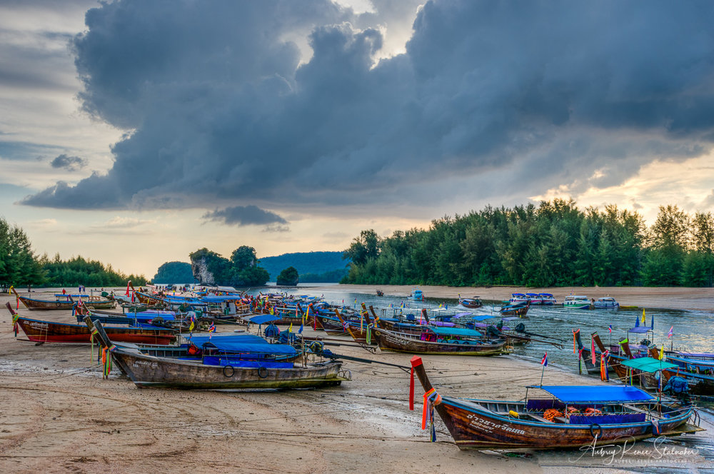 Longtail boats beached at low tide under a sunset over Krabi, Thailand