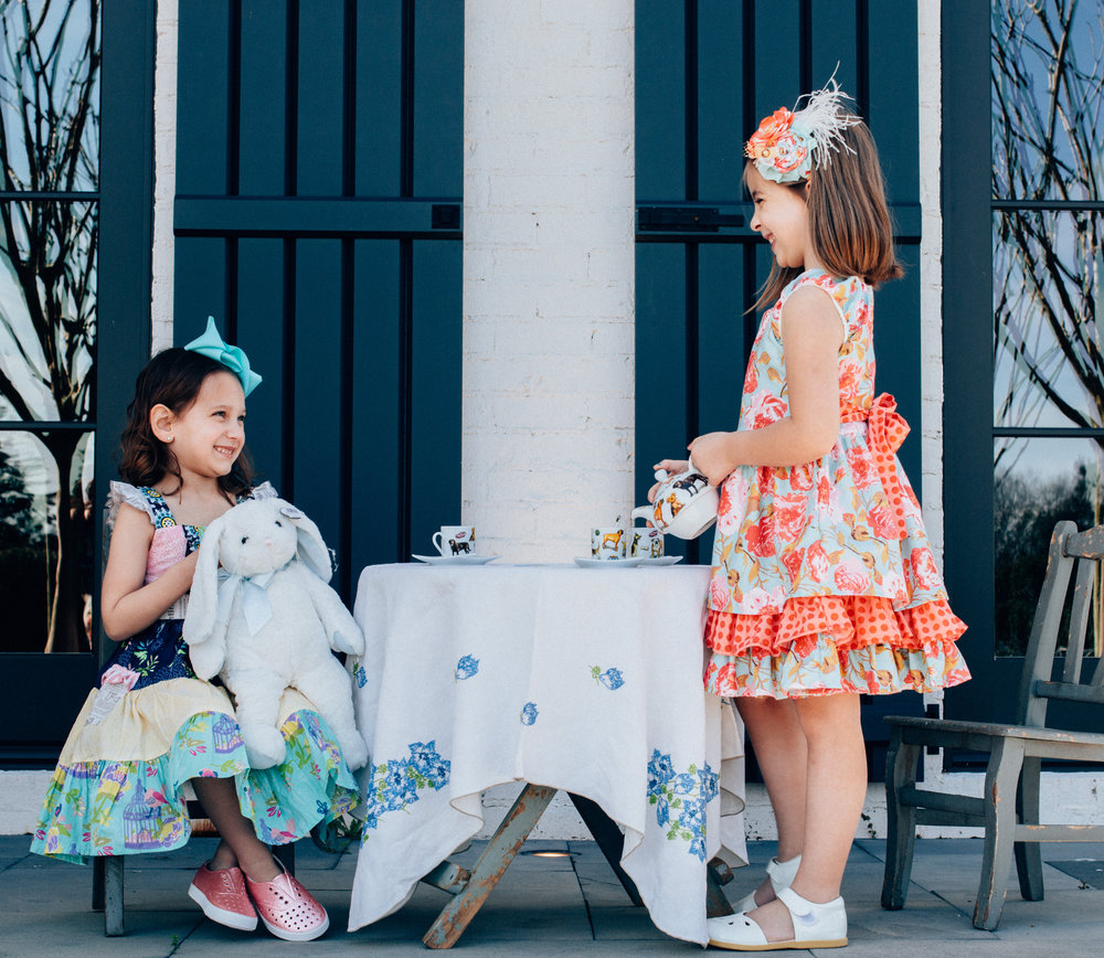 """Zoe (Mimi's Boutique, The Avenue):  Mustard Pie """"quilt"""" dress with cap sleeve, teal grosgrain ribbon, and Native pink glitter sneakers.   Lilly Broox (Mimi's Closet, The Avenue):   Mustard Pie cabbage rose print dress with matching fascinator headband, and Livie and Luca cream Mary Janes."""