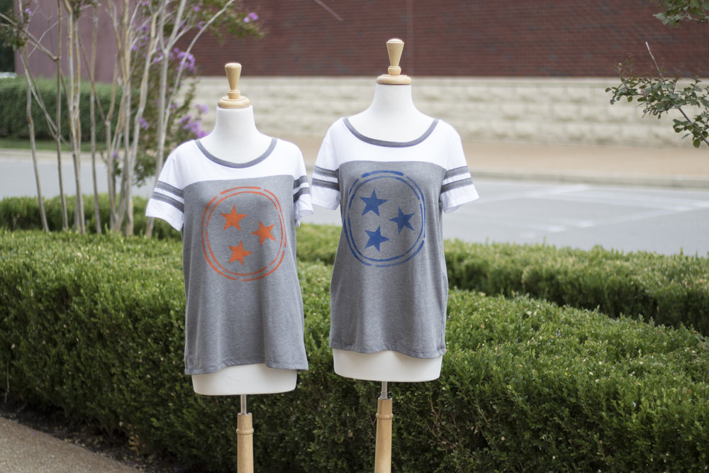 The softest vintage style jersey tee with a hand-painted Tristar design. Available in Royal Blue and Orange at MiMi's Boutique. $34