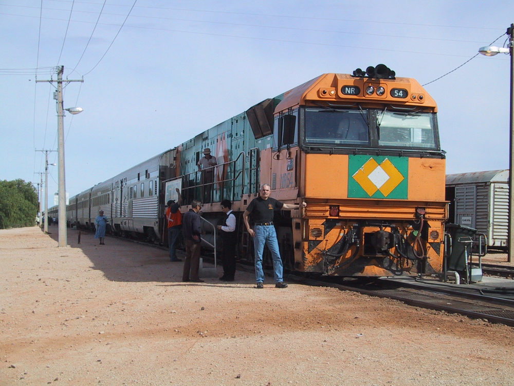 "The ""Indian Pacific"" at a service stop in Cook, South Australia, taking on drinking water. That's me holding up the locomotive. Photo by Bradford Wing"