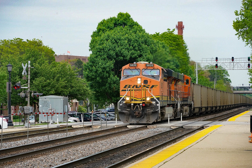 A BNSF coal unit train going through the Hinsdale Metra station. Leading is a ES44AC locomotive built by General Electric.