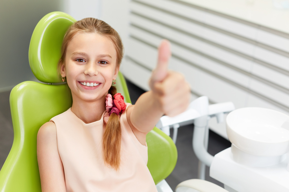 child giving thumbs up in the dental chair
