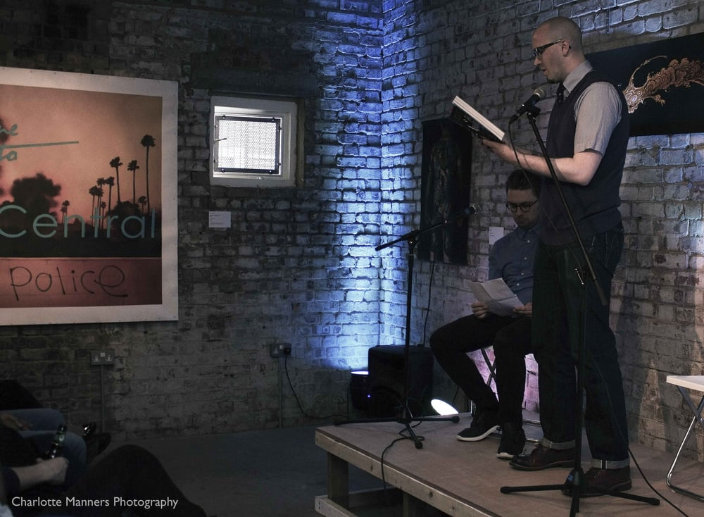 Flanked by author David Whitehouse, Ryan Gattis reads from  All Involved  in East London, 2015.