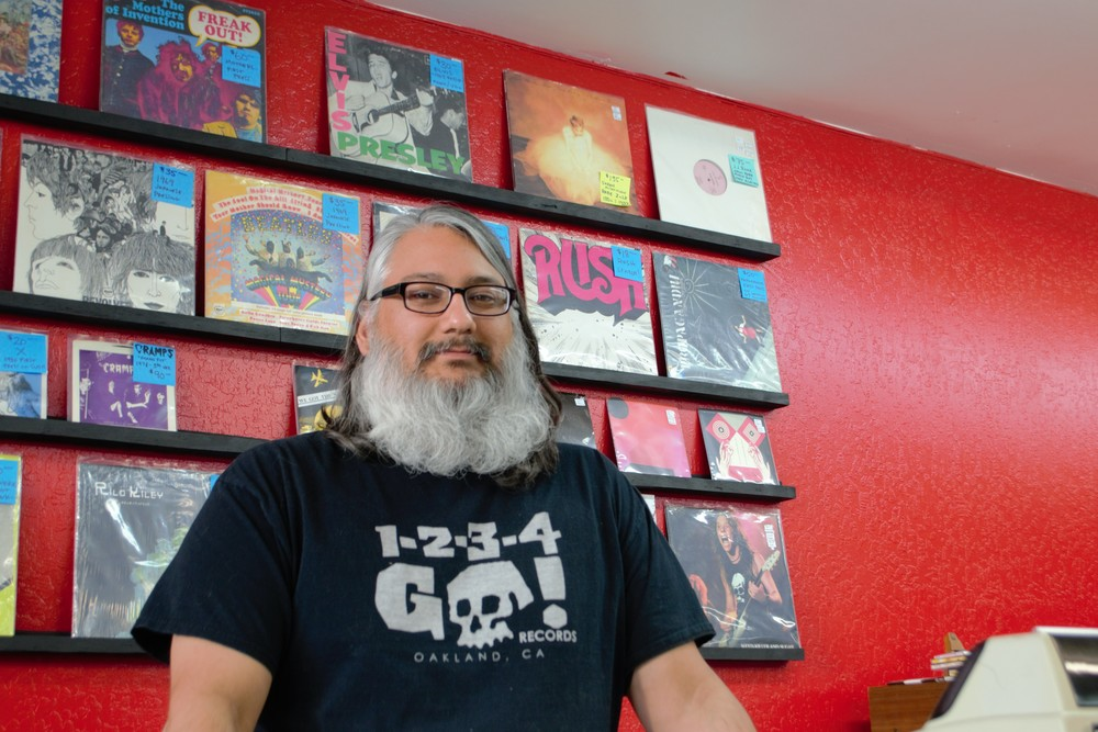 Gabriel Torres, owner of Spectre Records on Wells Avenue, prides himself in his smaller, select music collection. Spectre Records moved in December 2015 from Center Street to its current location. CREDIT: Natalie Van Hoozer for Noticiero Móvil.