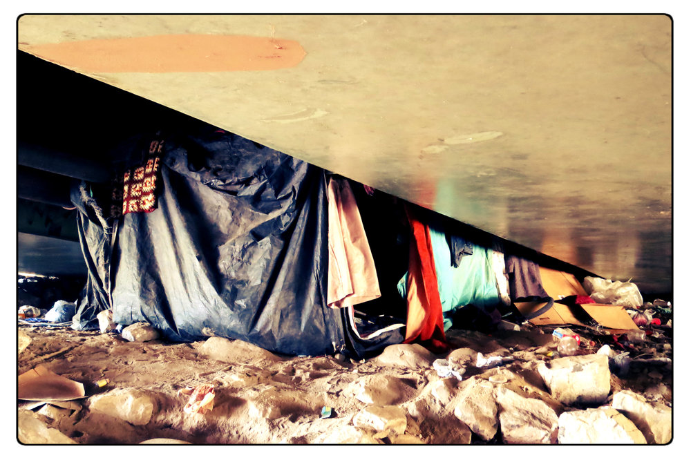 Some of Brian's neighbors live inside tents, but Brian uses just a blanket to sleep.
