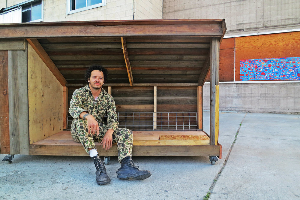 "Chris Wyatt Scott is worn down, but satisfied, as he completed an extremely sturdy, functional, and nicely designed ""teeny house"" complete with a lockable storage box in just one day with discarded wood and materials."
