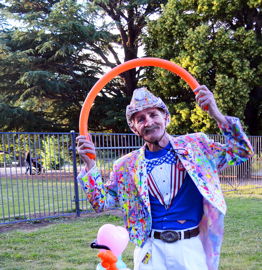 "Local balloon artist, I.B. Funny, poses for a picture while making balloon creations for kids at Idlewild Park. ""This is a classic pose that I like,"" he says as he gets into position with a smile on his face. I.B. Funny frequents local events to share his craft of balloon making."