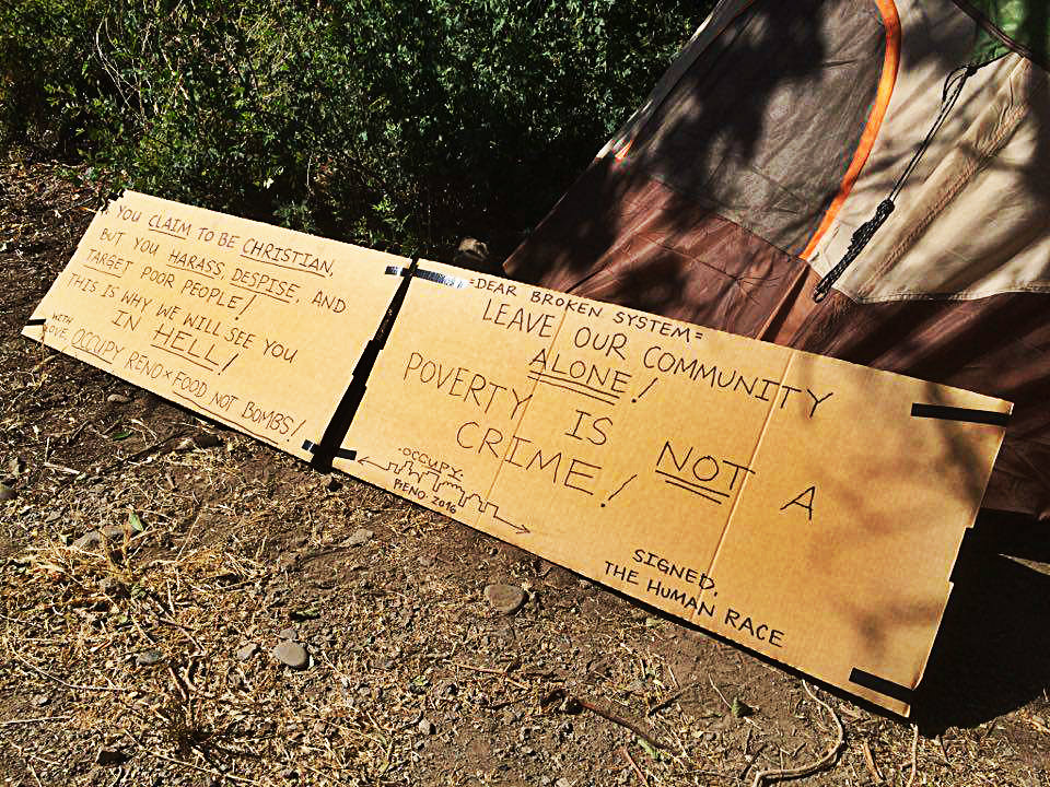 The activist camp is set up with a cardboard message for police. Photo provided by Food Not Bombs.