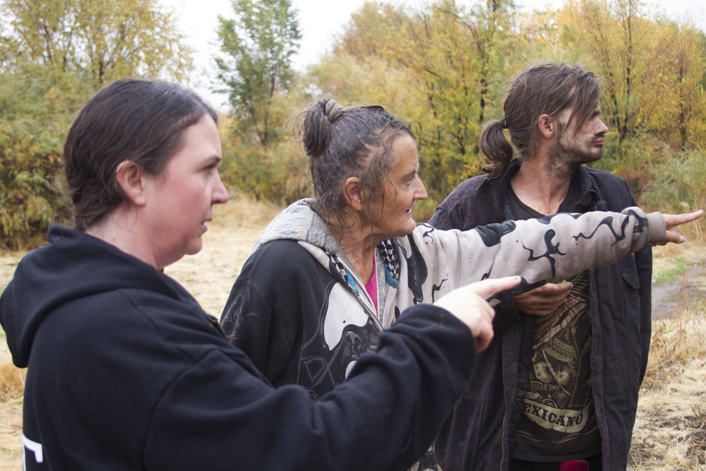 Activist Jennifer Cassady (left) is shown areas where chainsaws recently cut down tree parts which were providing shelter for homeless camp sites along the Truckee River.