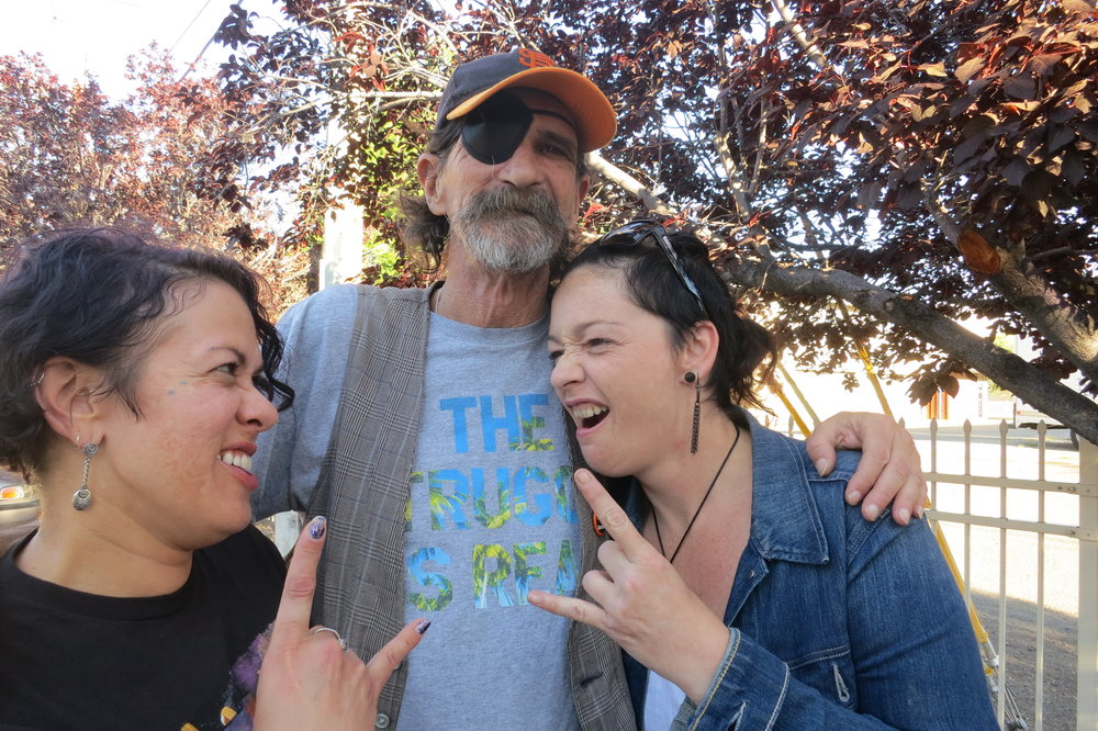 "Stephen Popovich, 61, poses with two of his Houris, Lisa Lee (left) and Wendy Wiglesworth (right), as part of the VOICE writing workshop.  An electrician and construction worker, he arrived in Reno from the Bay Area in the late 1960s, and says he got into a downward spiral of ""bartending, coke and bad romances.""  He's now on Social Security, ""a couple of bills shy of being broke already"", but lives in an apartment, writes on a computer, engages in social media, and manages the therapeutic writing workshop.  He is also battling cancer and had his eye removed earlier this year. Houris is a word traditionally associated with beings in Islamic mythology which is the title of this essay.  ""I always played around with writing and this group provided me with this opportunity,"" he says of VOICE (Voices Of Inspiration, Courage, and Empowerment). ""It has opened me back to the world."""