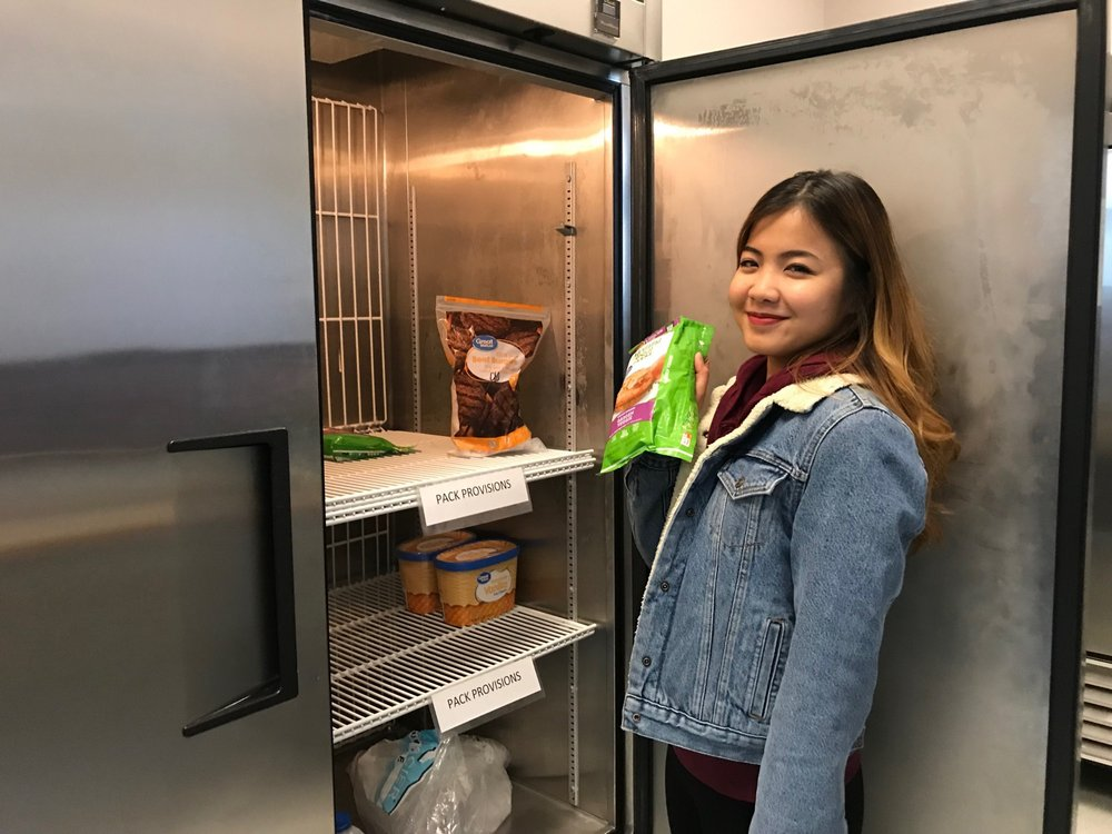 Pack Provisions student coordinator Karissa Mendaros gives a tour of the kitchen on site that has big coolers with frozen food free for students. Photo by Lucia Starbuck.