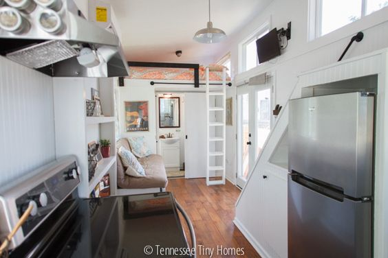 Tall fridge under staircase with storage.  Music City Tiny House