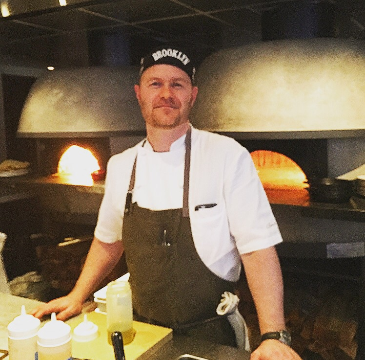 Chef de Cuisine Timothy Caspare in front of the wood-burning ovens,  manning the open kitchen