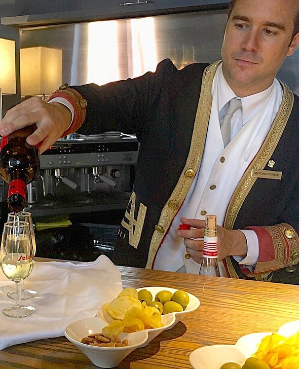Antonio from the amazing and historic  Hotel Alfonso XIII in Seville Pouring a refreshing Fino Sherry to have before dinner with olives, potato chips and marcona almonds.  Fantastic!!