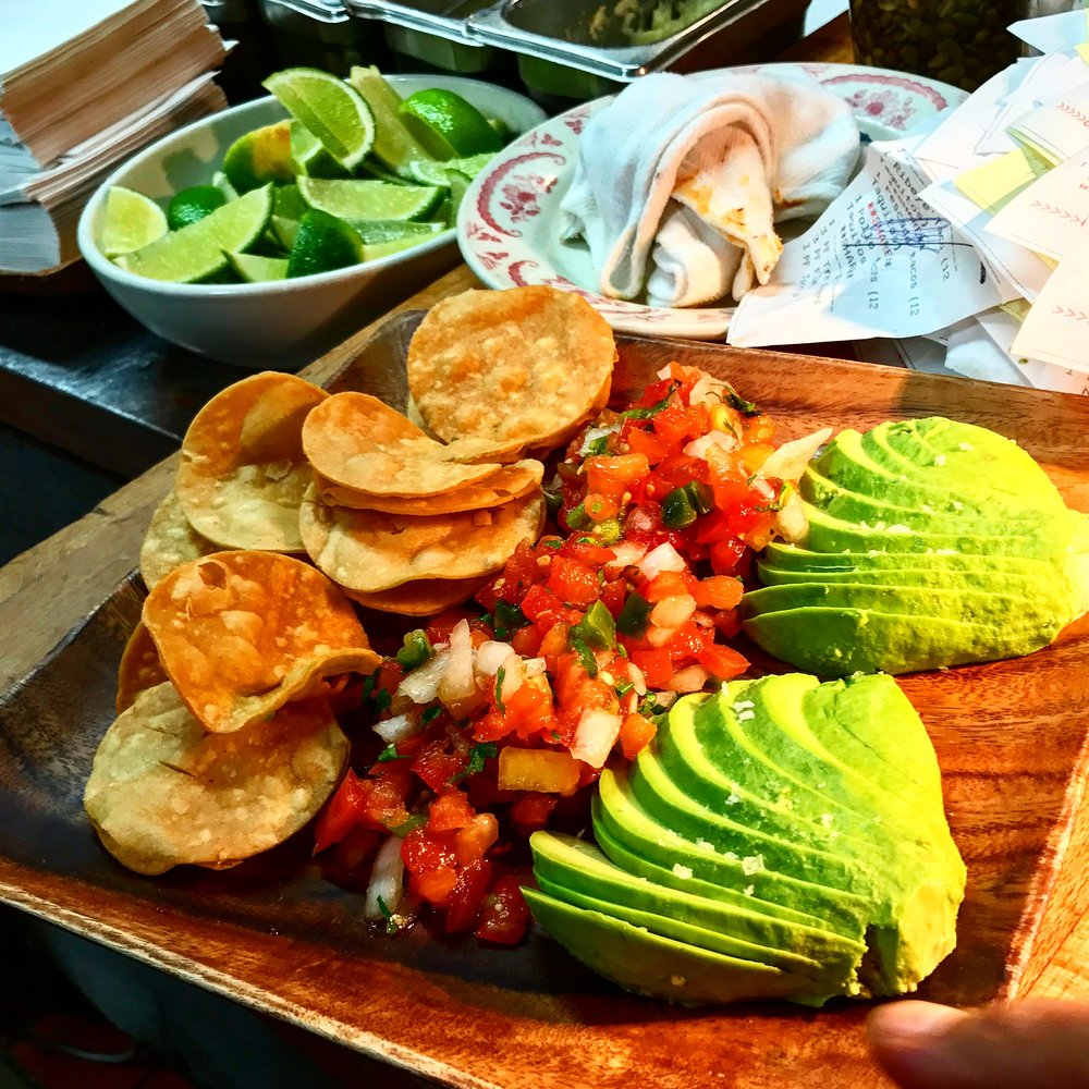 Homemade tortilla chips with avocado and salsa, ready to leave the kitchen at La Esquina