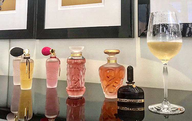 Stunnning Lalique perfume bottles next to a 100 Points Universal glass filled with Domaine Carneros bubbly.