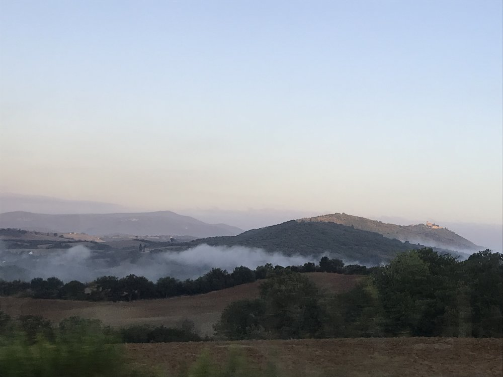 The early morning fog lies in the valleys of Montecucco.