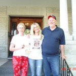 Joy, holding our book, Lisa and Don in front of the Leggett House.