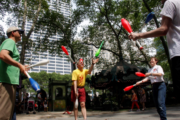 A juggling instructor, left, facilitates a group juggle session in Bryant Park, NYC.