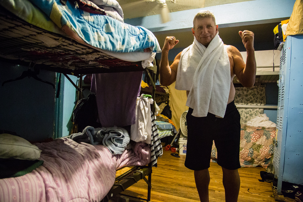 Daniel, an immigrant from El Salvador, flexes his muscles after a shower.