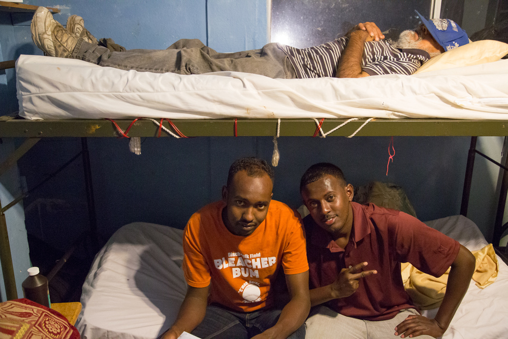 Two immigrants from Ethiopia prepare for bed before curfew.