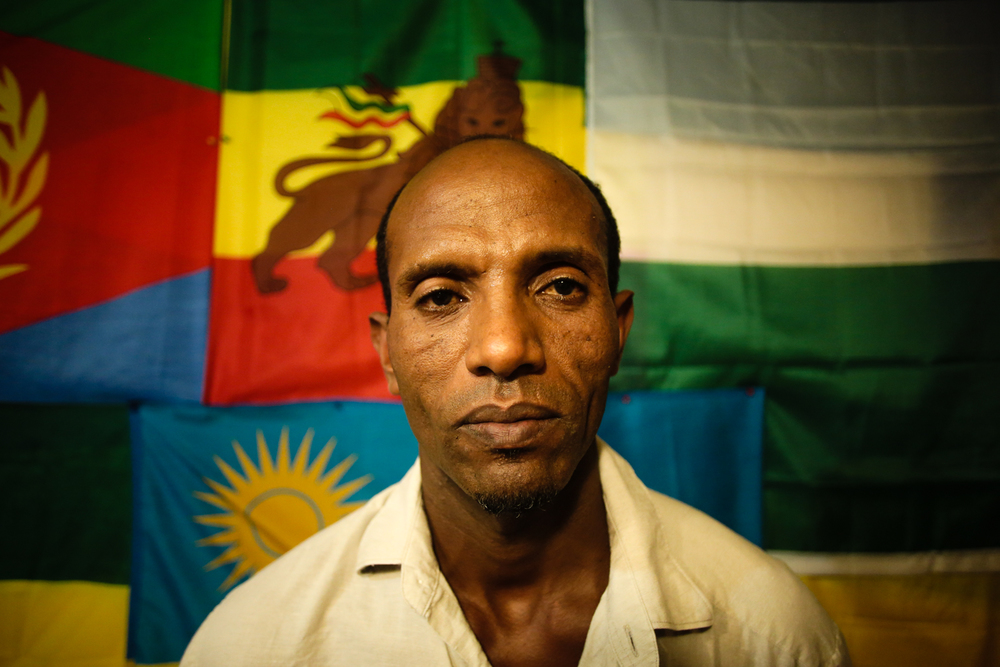 Hilut, an Eritrean immigrant asks to pose for a portrait in front of his nation's flag.