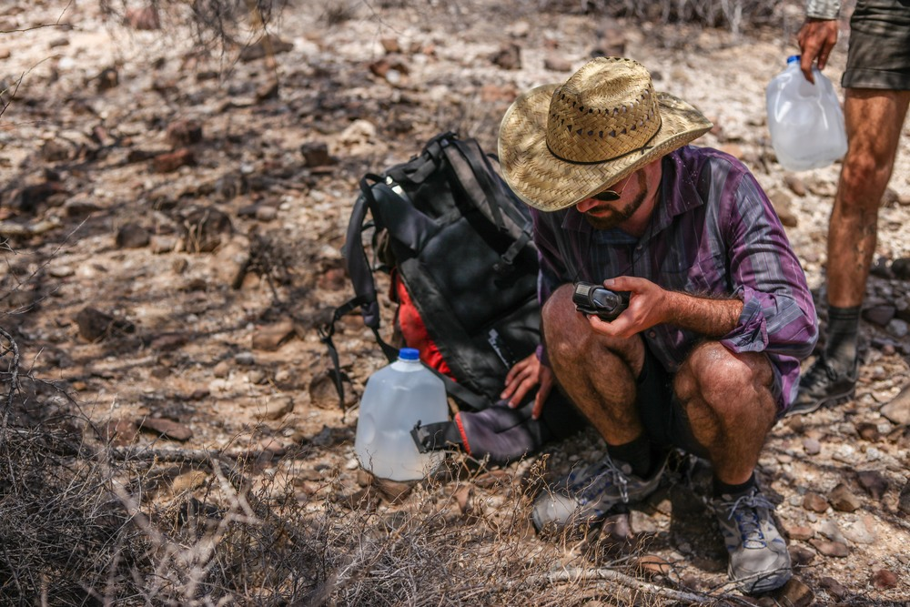 While bushwhacking, J uses GPS to find the waypoint and ensure that the team doesn't get lost.