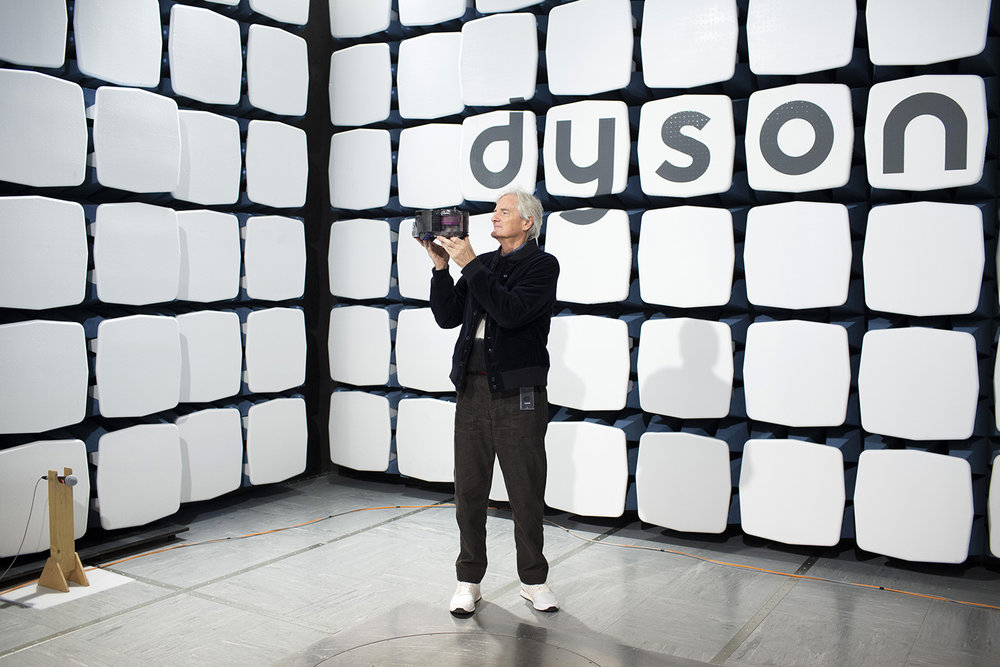 Portrait of Sir James Dyson holding a robotic vacuum.