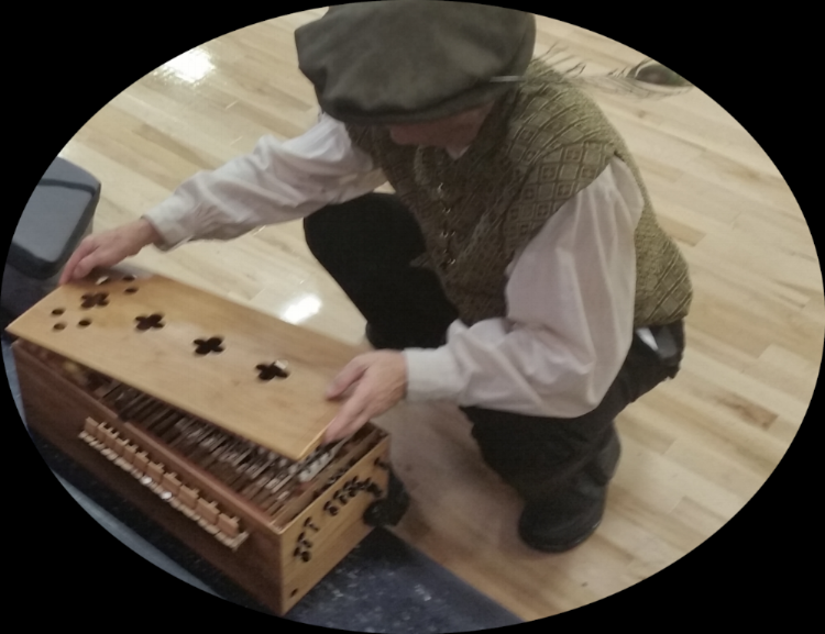 Cover coming off the medieval hurdy-gurdy I built. Note the miracle hat with magic feather.