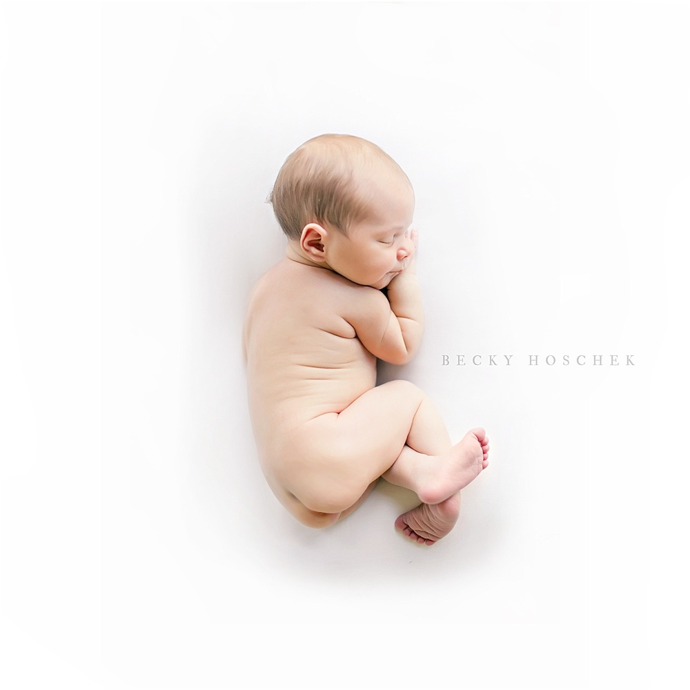 naked natural newborn baby girl simple relaxed pose on solid white background